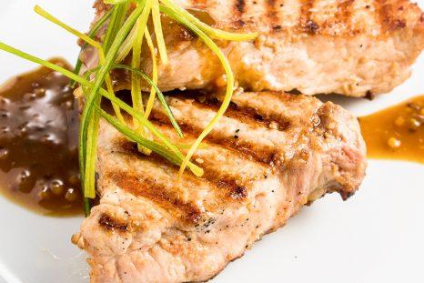 Deux steaks à base d'alternative végétale posés sur une assiette blanche avec une sauce